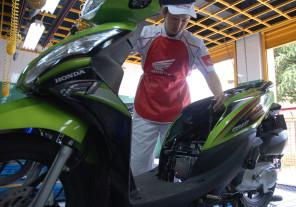 Mekanik AHASS sedang melakukan service sepeda motor Honda Spacy PGM-FI.
