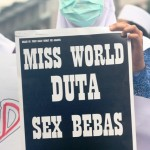 Pelajar memperlihatkan poster penolakan miss world 2013. (Foto: Ujang Komar/SJ)